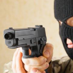 Man in black mask holding gun before him