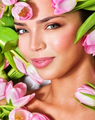 Beautiful woman's face surrounded by pink tulips. Spring Flower.