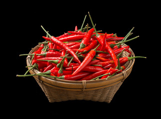 Red chillies in a basket isolated on black background
