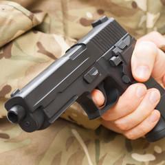 Man in black mask holding gun behind his back
