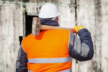 Worker with sledge hammer against the wall