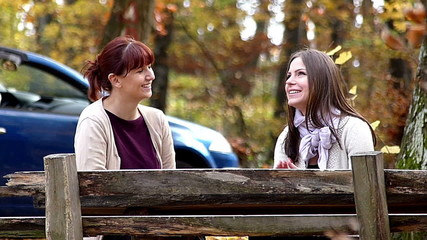 Happy young girls talking on bench in forest