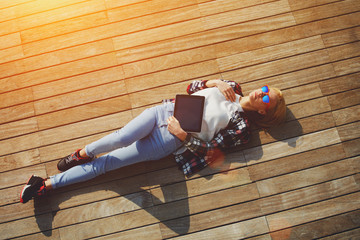 Carefree young woman lying on the wooden jetty in the sun