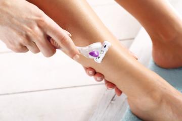 Kobieta goli nogi ręczną maszynką do golenia
