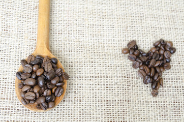 Wooden spoon full with roasted coffee beans and a coffee heart