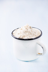 Heap of wheat flour in white vintage cup
