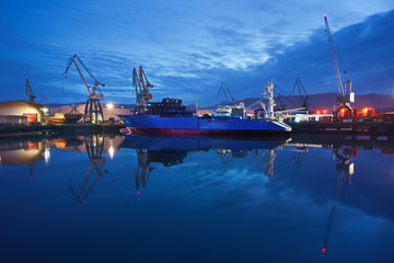 dock with cranes and ship at night