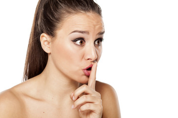 Young woman with finger on her lips. Silent gesture.