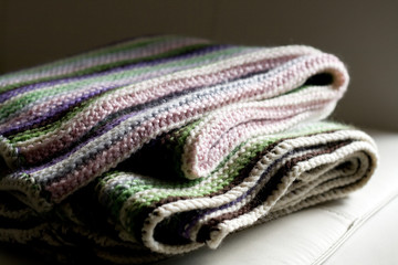 Knitting striped rug with white, purple, green and pink stripes