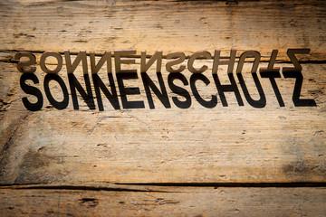 Buchstaben aus Holz bilden das Wort Sonnenschutz