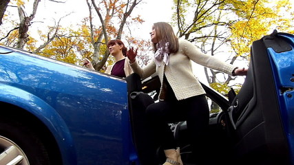 Two young girls teasing guy while he is pushing a car