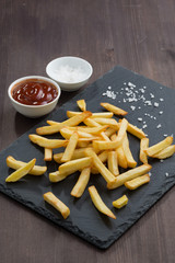 French fries and tomato sauce on a blackboard, vertical