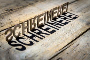 Buchstaben aus Holz bilden das Wort Schreinerei