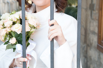 bride with flowers behind bars