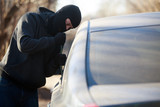 Thief stealing automobile car at daylight street in city