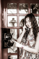 Thai girl is talking with an old-fashion phone in black and whit