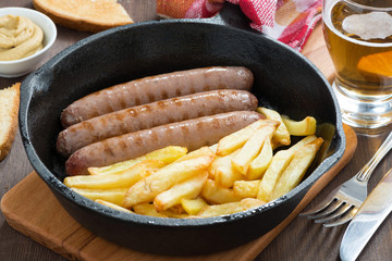 lunch with grilled sausages, French fries, toast and beer