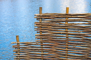 Wicker fence on a background of water