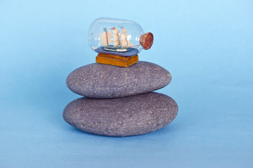 small ship sailboat model in glass bottle on sea stone