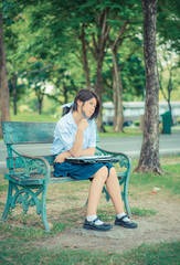 Cute Thai schoolgirl is studying and imagine something on a benc