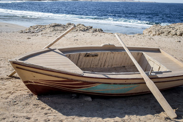 Wooden empty boat with two oars on beach