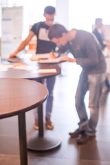 Two persons writing on table, blurred