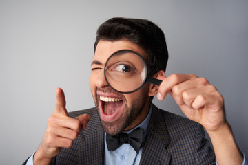 Smiling man holding magnifier near eye and pointing at camera