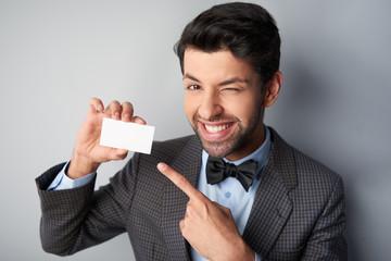 Smiling man pointing at blank visiting card and winking