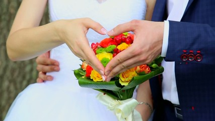 Close up of couple making heart shape with hands in wedding day