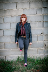 Rebellious teenager girl with red hair leaning on a wall
