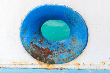 Empty blue hawse in old rusted ship hull