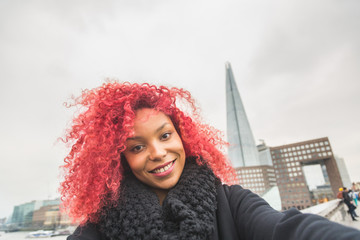 Girl taking selfie in London with Shard skyscraper on background
