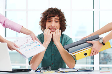 Scared overworked young businessman with hands around him