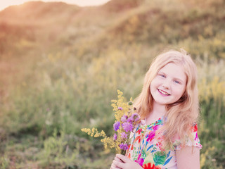 happy blond girl on meadow at sunset