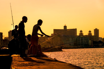 Silhouette of young boys fishing at sunset in Havana