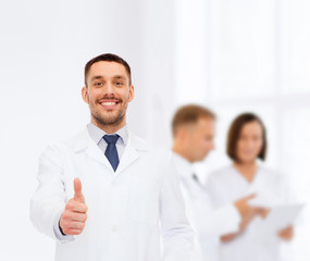 smiling male doctor showing thumbs up
