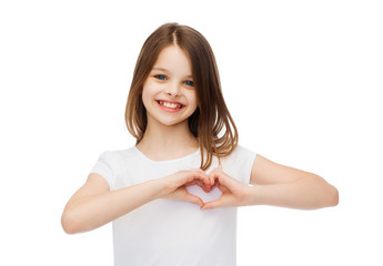 smiling little girl showing heart with hands