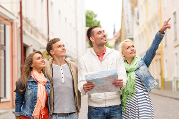 group of smiling friends with map exploring city