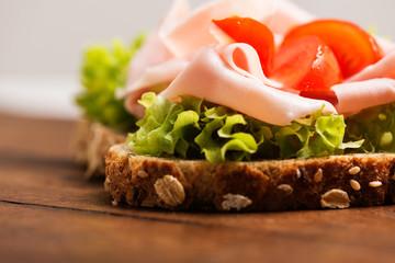 Ham sandwich with tomato on wood