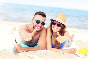 Happy couple lying on the beach