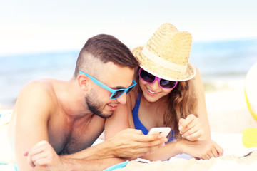 Couple using smartphone at the beach