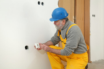 Construction site, electrician install electrical plug to wall