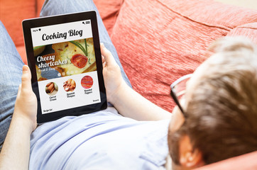 hipster on the sofa with cooking blog tablet