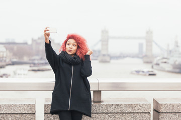 Girl taking selfie in London with Tower Bridge on background