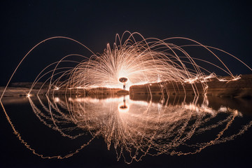 Spinning fire with the reflection in the water