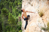 Young male rock climber on challenging route on cliff