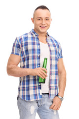 Relaxed young man holding a bottle of beer