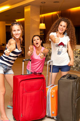 Three girls with suitcases on a journey