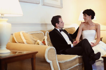 groom and bride sitting on a couch