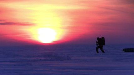One man go to sunset on snow desert